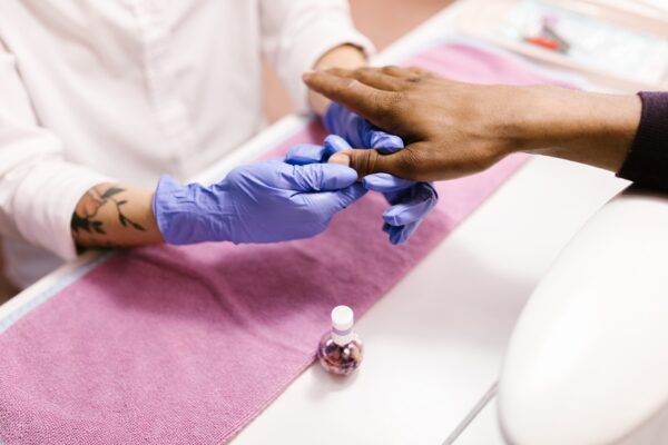 A nail technician applying cuticle oil onto a client's nails